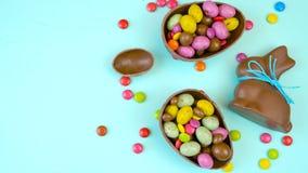 Ευτυχές υπόβαθρο σοκολάτας Πάσχας παρακμιακό υπερυψωμένο με τα αυγά και την καραμέλα Πάσχας απόθεμα βίντεο