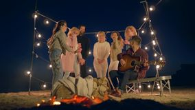 Ευτυχές υπόλοιπο, ομάδα νέων που χορεύουν και που τραγουδούν κοντά στην πυρά προσκόπων στην παραλία στο φωτισμό των γιρλαντών φιλμ μικρού μήκους