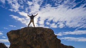 Ευτυχές φίλαθλο άτομο με το σακίδιο πλάτης και αυξημένος επάνω στα όπλα που στέκονται και στο βράχο και που εξετάζουν την ακτή κα στοκ φωτογραφίες