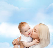 Ευτυχές φιλώντας χαμογελώντας μωρό μητέρων Στοκ φωτογραφία με δικαίωμα ελεύθερης χρήσης