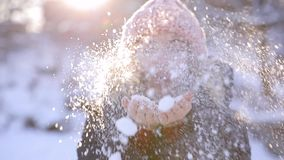 Ευτυχές φυσώντας χιόνι γυναικών από τα χέρια απόθεμα βίντεο