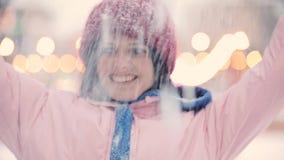 Ευτυχές φυσώντας χιόνι γυναικών στο χειμώνα, σε αργή κίνηση απόθεμα βίντεο