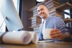 Ευτυχές φλυτζάνι εκμετάλλευσης επιχειρηματιών στο γραφείο υπολογιστών Στοκ Εικόνα