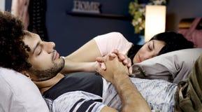 Ευτυχές χέρι εκμετάλλευσης ζευγών ερωτευμένο κοισμένος στο κρεβάτι Στοκ εικόνα με δικαίωμα ελεύθερης χρήσης