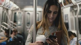 Ευτυχές χαλαρωμένο βέβαιο κορίτσι blogger στο υπόγειο τρένο που χρησιμοποιεί το φορέα app μουσικής smartphone που χαμογελά με το  φιλμ μικρού μήκους