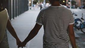 Ευτυχές χαλαρωμένο ενήλικο ρομαντικό ζεύγος που περπατά κατά μήκος της οδού πόλεων της Νέας Υόρκης βραδιού που κρατά μαζί τα χέρι απόθεμα βίντεο