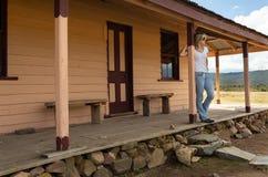 Ευτυχές χαλαρωμένο θηλυκό στη βεράντα του παλαιού σπιτιού ξυλείας στην αγροτική επαρχία στοκ εικόνες