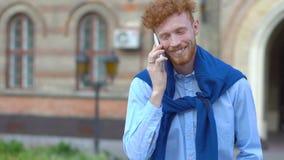 Ευτυχές χαμογελώντας άτομο με τη σγουρή τρίχα πιπεροριζών και γενειάδα που μιλά μέσω του κινητού τηλεφώνου στο θολωμένο υπόβαθρο απόθεμα βίντεο