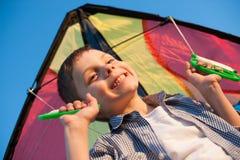 Ευτυχές χαμογελώντας αγόρι με το ζωηρόχρωμο ικτίνο πίσω από τους ώμους στο υπόβαθρο μπλε ουρανού στο ηλιοβασίλεμα Στοκ Φωτογραφία