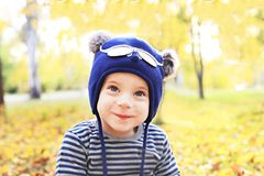 Ευτυχές χαμογελώντας αστείο μικρό παιδί που φορά ένα χαριτωμένο καπέλο υπαίθριο στο πάρκο φθινοπώρου Ευτυχής παιδική ηλικία, όνει στοκ φωτογραφία με δικαίωμα ελεύθερης χρήσης