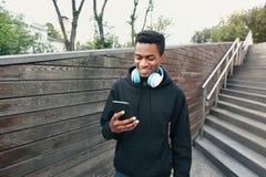 Ευτυχές χαμογελώντας αφρικανικό άτομο πορτρέτου με το τηλέφωνο, ακουστικά που ακούει τη μουσική που φορά το μαύρο hoodie, που περ στοκ εικόνες