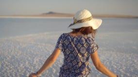 Ευτυχές χαμογελώντας κορίτσι που απολαμβάνει ένα ηλιοβασίλεμα, έναν χορό και τα γέλια στην έκταση της αλατισμένης λίμνης απόθεμα βίντεο