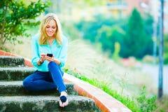 Ευτυχές χαμογελώντας κορίτσι που γράφει ένα μήνυμα στοκ φωτογραφία με δικαίωμα ελεύθερης χρήσης