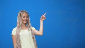 Ευτυχές χαμογελώντας κορίτσι που δείχνει το δάχτυλο μακριά στο copyspace και που κάνει την έγκριση της χειρονομίας που απομονώνετ φιλμ μικρού μήκους
