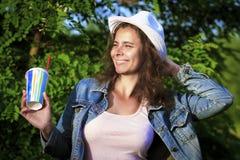 Ευτυχές χαμογελώντας κορίτσι στη φύση με το κοκτέιλ Ελκυστικό κορίτσι στο σακάκι καπέλων και τζιν στο πράσινο υπόβαθρο δέντρων Στοκ φωτογραφία με δικαίωμα ελεύθερης χρήσης