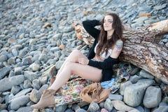 Ευτυχές χαμογελώντας κορίτσι brunette brunette στη boppy κομψή συνεδρίαση ύφους στις γκρίζες πέτρες Στοκ Φωτογραφίες