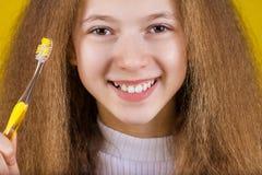 Ευτυχές, χαμογελώντας μικρό κορίτσι που βουρτσίζει τα δόντια της με την οδοντόπαστα de στοκ εικόνα