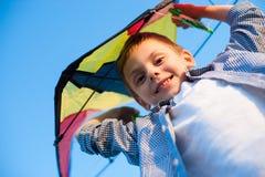 Ευτυχές χαμογελώντας μικρό παιδί με τον ικτίνο παιχνιδιών επάνω από το κεφάλι στο υπόβαθρο μπλε ουρανού στη θερινή ηλιόλουστη ημέ Στοκ φωτογραφία με δικαίωμα ελεύθερης χρήσης