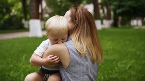 Ευτυχές, χαμογελώντας ξανθό αγόρι που τρέχει ευτυχώς με τη γλώσσα του που κρεμά έξω στο mom του Χαρούμενες στιγμές Αγκάλιασμα μητ φιλμ μικρού μήκους