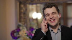 Ευτυχές χαμογελώντας άτομο που κουβεντιάζει σε έναν κινητό απόθεμα βίντεο