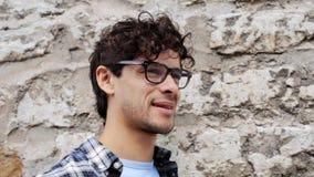 Ευτυχές χαμογελώντας άτομο eyeglasses πέρα από τον τοίχο 20 οδών απόθεμα βίντεο