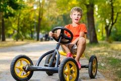 Ευτυχές χαμογελώντας αγόρι που οδηγεί ένα αυτοκίνητο παιχνιδιών υπαίθριο Στοκ Φωτογραφία