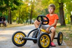 Ευτυχές χαμογελώντας αγόρι που οδηγεί ένα αυτοκίνητο παιχνιδιών υπαίθριο Στοκ Εικόνες