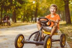 Ευτυχές χαμογελώντας αγόρι που οδηγεί ένα αυτοκίνητο παιχνιδιών υπαίθριο Στοκ εικόνες με δικαίωμα ελεύθερης χρήσης