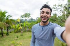 Ευτυχές χαμογελώντας λατινικό άτομο που παίρνει τη φωτογραφία Selfie πέρα από το πράσινο τροπικό τοπίο τροπικών δασών Στοκ εικόνες με δικαίωμα ελεύθερης χρήσης