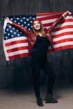 Ευτυχές χαμογελώντας κορίτσι με την ΑΜΕΡΙΚΑΝΙΚΗ σημαία πίσω από την πλάτη στοκ εικόνα με δικαίωμα ελεύθερης χρήσης