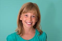 Ευτυχές χαμογελώντας μικρό κορίτσι α στο τυρκουάζ υπόβαθρο συγκινήσεις Στοκ εικόνες με δικαίωμα ελεύθερης χρήσης