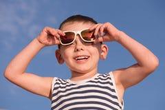 Ευτυχές χαμογελώντας μικρό παιδί που φορά τα γυαλιά ηλίου και το πουκάμισο στο υπόβαθρο μπλε ουρανού Στοκ εικόνα με δικαίωμα ελεύθερης χρήσης