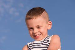 Ευτυχές χαμογελώντας μικρό παιδί που φορά το πουκάμισο λωρίδων ναυτικών στο υπόβαθρο μπλε ουρανού Στοκ φωτογραφία με δικαίωμα ελεύθερης χρήσης