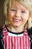 Ευτυχές, χαμογελώντας παιδί με το ακατάστατο πρόσωπο σοκολάτας Στοκ Φωτογραφία