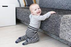Ευτυχές χαμογελώντας χαριτωμένο κοριτσάκι 6 μηνών που προσπαθεί να σηκωθεί Στοκ εικόνα με δικαίωμα ελεύθερης χρήσης