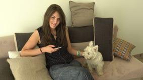 Ευτυχές χαμόγελο γυναικών εξετάζοντας τη κάμερα και κτυπώντας το κατοικίδιο ζώο σκυλιών της φιλμ μικρού μήκους