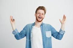 Ευτυχές χαμόγελο νεαρών άνδρων που ακούει τη μουσική ροής στο τραγούδι ακουστικών που εξετάζει τη κάμερα πέρα από το άσπρο υπόβαθ Στοκ Εικόνα