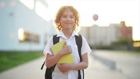 Ευτυχές χαριτωμένο έξυπνο αγόρι με τη σχολική τσάντα και βιβλίο στο χέρι του backpack σύγχρονο Το παιδί είναι έτοιμο να απαντήσει απόθεμα βίντεο