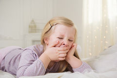 Ευτυχές χαριτωμένο κορίτσι παιδιών που χασμουριέται στο κρεβάτι Στοκ Φωτογραφία