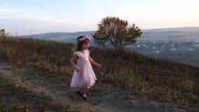 Ευτυχές χαριτωμένο κορίτσι που τρέχει από το λόφο Καταπληκτικό τοπίο στο υπόβαθρο απόθεμα βίντεο