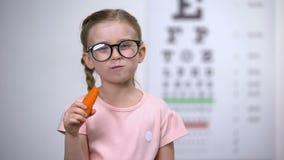 Ευτυχές χαριτωμένο κορίτσι eyeglasses που τρώει το καρότο, βιταμίνη Α για το καλό όραμα, υγεία απόθεμα βίντεο