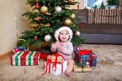 Ευτυχές χαριτωμένο κοριτσάκι στα δώρα Χριστουγέννων εκμετάλλευσης καπέλων Άγιου Βασίλη στο χριστουγεννιάτικο δέντρο στο σπίτι στοκ φωτογραφία