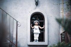 Ευτυχές χαριτωμένο μικρό κορίτσι που χαμογελά και που υπερασπίζεται το παράθυρο στοκ φωτογραφία