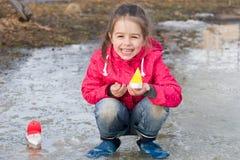 Ευτυχές χαριτωμένο μικρό κορίτσι στις μπότες βροχής που παίζει με τον κολπίσκο σκαφών την άνοιξη που στέκεται στο νερό Στοκ Εικόνες