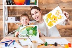 Ευτυχές χαριτωμένο μικρό παιδί και η μητέρα του που παρουσιάζουν χρώματά τους Στοκ εικόνες με δικαίωμα ελεύθερης χρήσης