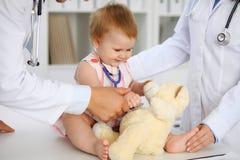 Ευτυχές χαριτωμένο μωρό στο διαγωνισμό υγείας στο γραφείο γιατρών ` s Το κορίτσι μικρών παιδιών κάθεται και κρατά το στηθοσκόπιο  Στοκ Φωτογραφία
