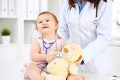 Ευτυχές χαριτωμένο μωρό στο διαγωνισμό υγείας στο γραφείο γιατρών ` s Το κορίτσι μικρών παιδιών κάθεται και κρατά το στηθοσκόπιο  Στοκ Εικόνα
