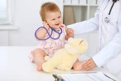 Ευτυχές χαριτωμένο μωρό στο διαγωνισμό υγείας στο γραφείο γιατρών ` s Το κορίτσι μικρών παιδιών κάθεται και κρατά το στηθοσκόπιο  Στοκ φωτογραφία με δικαίωμα ελεύθερης χρήσης