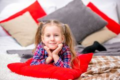 Ευτυχές χαριτωμένο νέο κορίτσι σε ένα ελεγμένο μπλε-κόκκινο φόρεμα που βρίσκεται στο κρεβάτι και το χαμόγελο στοκ εικόνα με δικαίωμα ελεύθερης χρήσης