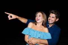 Ευτυχές χαρούμενο νέο ζεύγος που γελά και που δείχνει μακριά Στοκ εικόνες με δικαίωμα ελεύθερης χρήσης